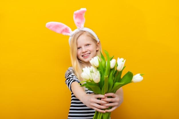 A menina de sorriso nas orelhas do coelho do coelho na cabeça com tulipas floresce o ramalhete no fundo amarelo.