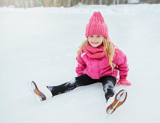 A menina de sorriso pequena patina e caiu no gelo no desgaste cor-de-rosa. exterior.