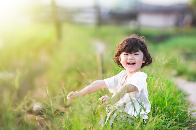 A menina de sorriso senta-se na grama