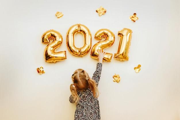 A menina decora a parede da casa com números dourados
