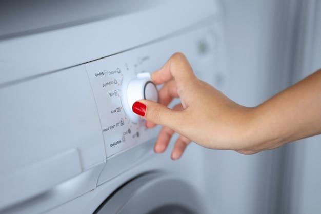 A menina define o programa de lavagem da máquina de lavar.