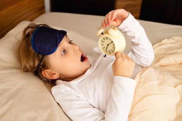 A menina deita na cama surpresa e chocada, assustada, está atrasada, o despertador está em suas mãos.
