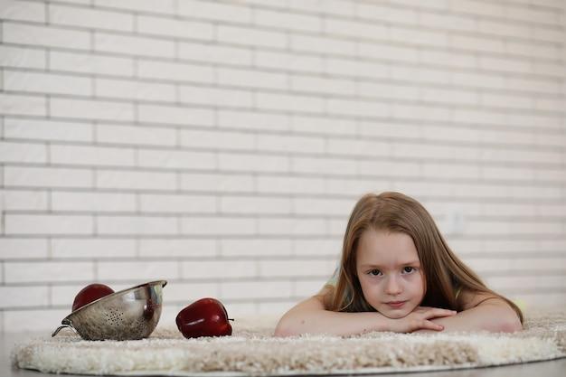 A menina deita-se no chão e come uma maçã