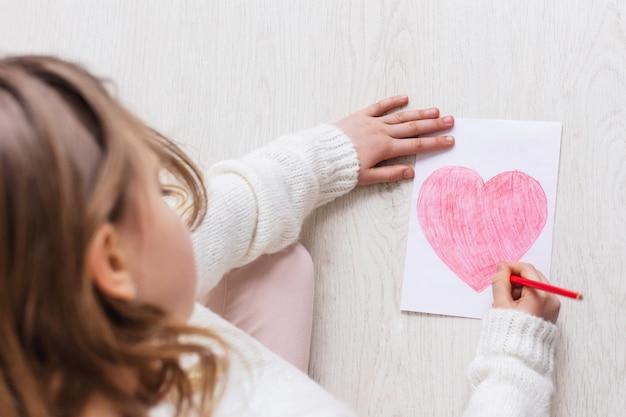A menina desenha um coração vermelho em um papel branco sobre um fundo de madeira no chão em casa. vista do topo. copie o espaço para o texto. dia das mães. o amor da criança por sua mãe.