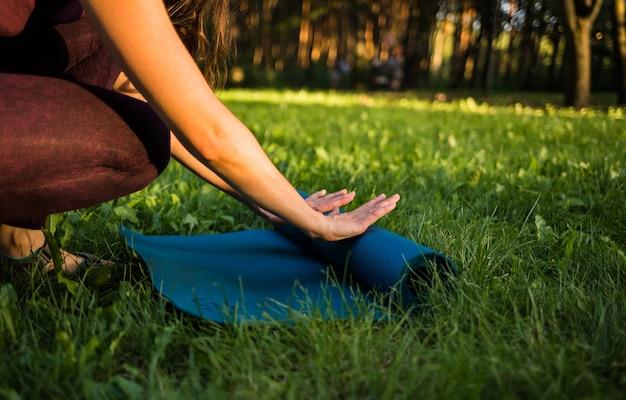 A menina desenrola um tapete de ioga na natureza