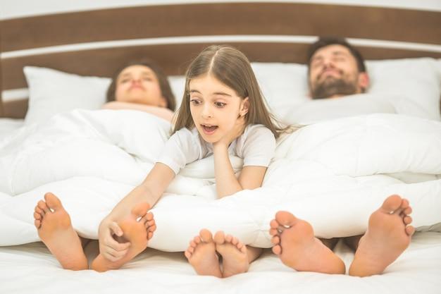 A menina divertida perto dos pais na cama