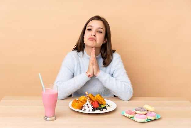 A menina do adolescente que come waffles isolados na parede bege mantém a palma unida. pessoa pede algo