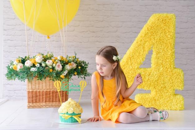 A menina do aniversário 4-5 anos velho está comemorando o aniversário em um estúdio estilizado decorado, no número 4 e no balão grande. estilo amarelo.