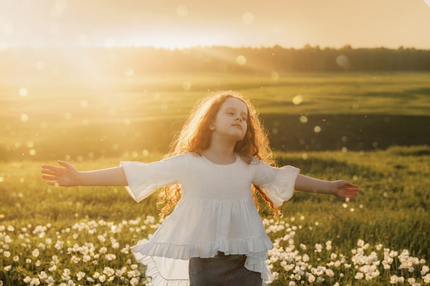 A menina do cabelo encaracolado fechou seus olhos e respirando com ar de sopro fresco no prado ao ar livre.