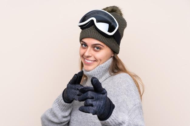 A menina do esquiador adolescente com óculos de snowboard aponta o dedo para você com uma expressão confiante