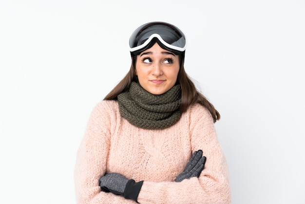 A menina do esquiador com vidros do snowboard sobre a parede branca isolada que faz dúvidas gesticula ao levantar os ombros