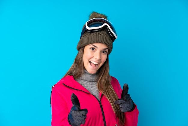 A menina do esquiador do adolescente com vidros do snowboard aponta o dedo em você