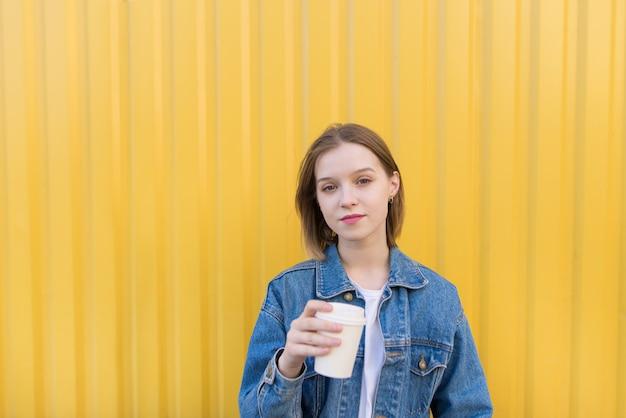 A menina do estudante está com a xícara de café em suas mãos no fundo amarelo e olha a câmera.