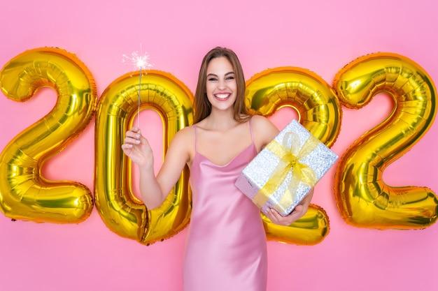 A menina do papai noel feliz levanta um brilho de champanhe enquanto segura uma caixa de presente com balões de ar de ano novo