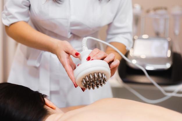 A menina do salão spa recebe uma massagem nas costas e pescoço, deita-se na mesa de cosmetologia, relaxada e aprecia o processo