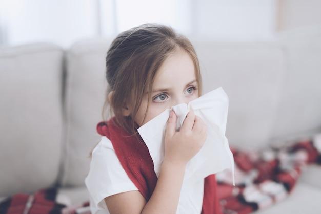 A menina doente senta-se em um sofá branco envolvido em um lenço vermelho.