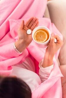 A menina doente toma comprimidos e bebe o chá em casa.