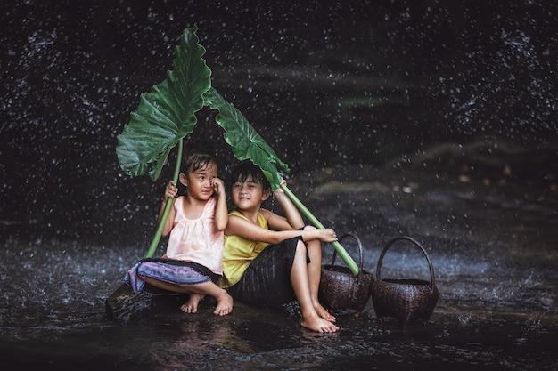 A menina dois bonita asiática joga a água no rio em tailândia.