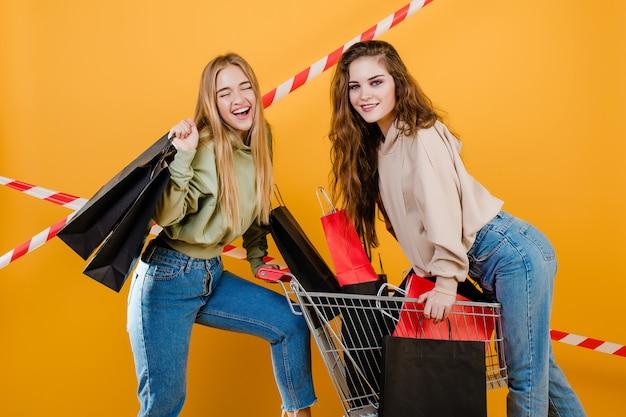A menina dois bonita de sorriso tem o carrinho com as sacolas coloridas e a fita de sinal isolada sobre o amarelo