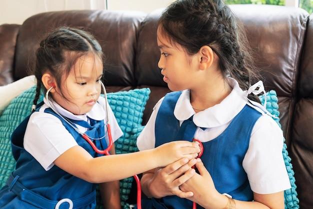 A menina dois está sorrindo e jogando o doutor com estetoscópio. kid e conceito de cuidados de saúde.