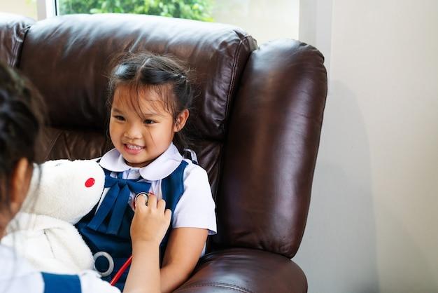 A menina dois está sorrindo e jogando o doutor com estetoscópio.