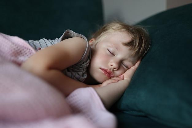 A menina dorme na cama com os braços cruzados sob a cabeça.