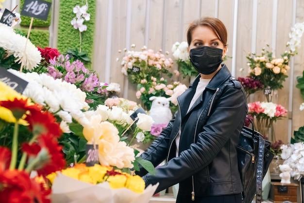 A menina durante uma doença pandêmica escolhe um presente em uma loja de flores. o conceito do feriado e a compra de um buquê durante o coronavírus