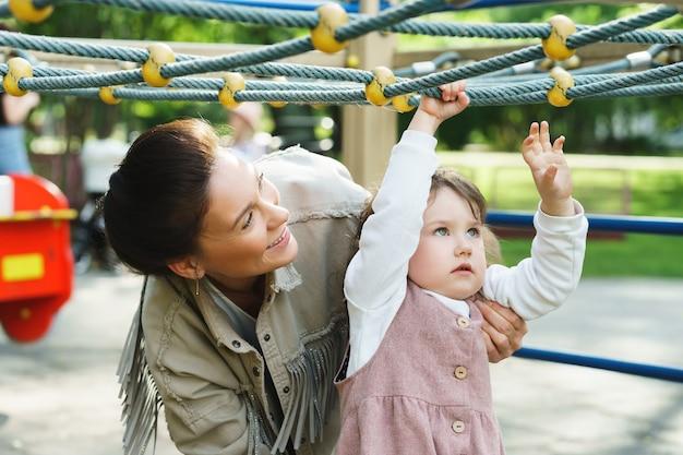 A menina e a mãe dela estão brincando no parquinho de um parque da cidade