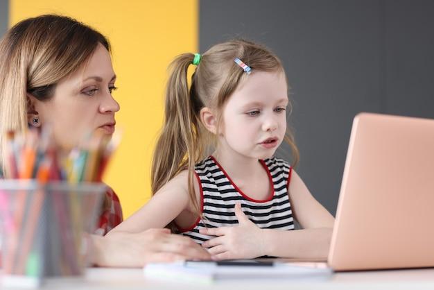 A menina e a mãe estão sentadas à mesa em frente à tela do laptop