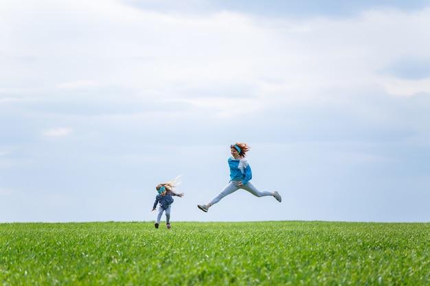 A menina e a mãe mulher correm e pulam, grama verde no campo, clima ensolarado de primavera, sorriso e alegria da criança, céu azul com nuvens