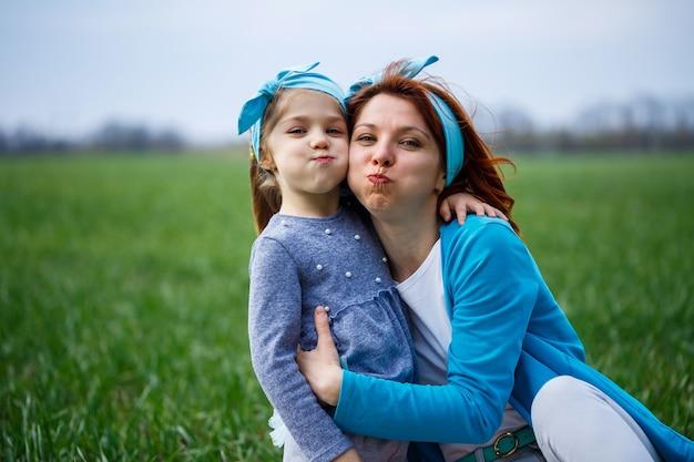 A menina e a mãe mulher estão sentadas na colcha, grama verde no campo, clima ensolarado de primavera, sorriso e alegria da criança, céu azul com nuvens