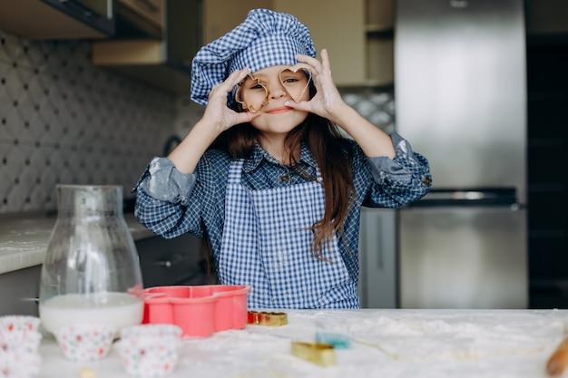 A menina é agitar a massa e ter um tempo engraçado na cozinha. - imagem