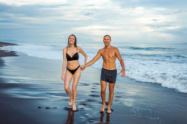 A menina e o homem caminham na praia em maiôs
