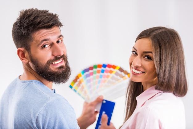 A menina e o homem escolhem cores novas para uma home nova.