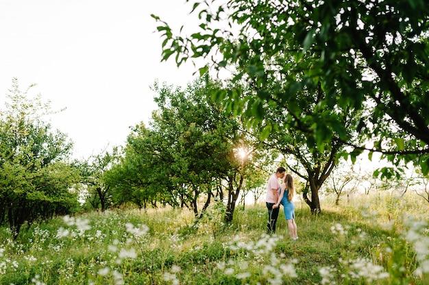 A menina e o marido grávidos beijam, estão no jardim com árvores.