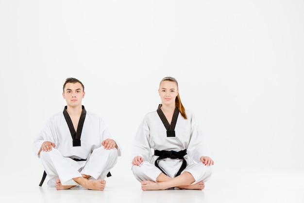A menina e o menino do karaté com faixas pretas