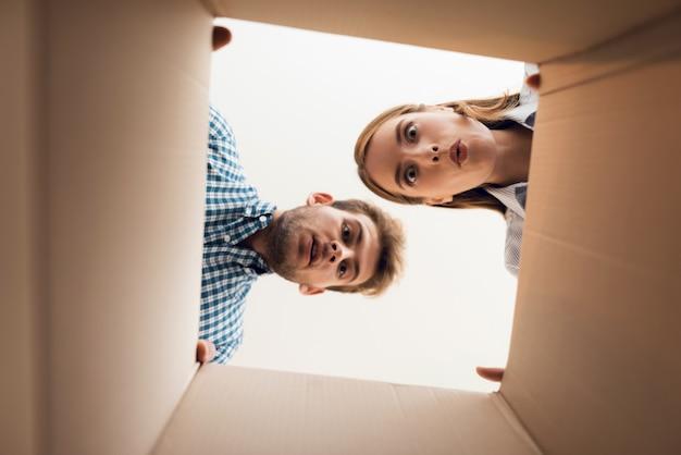 A menina e o menino estão olhando para a caixa vazia.