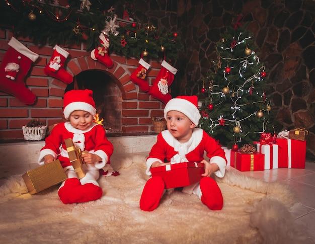 A menina e o menino estão sentados perto da lareira e a árvore de natal com caixas de presente. irmão e irmã em ternos de papai noel