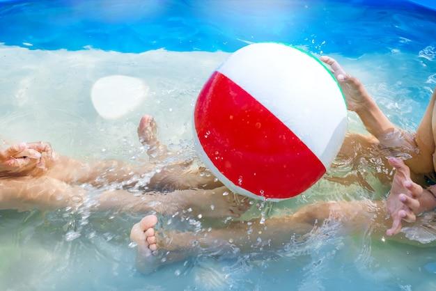 A menina e o menino jogam com a esfera na piscina ao ar livre.
