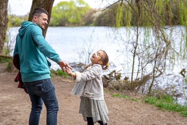 A menina e o pai estão andando na floresta de mãos dadas.