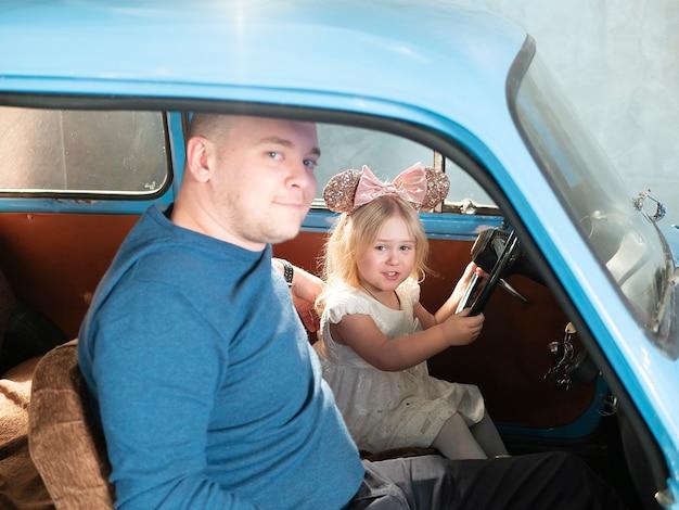 A menina e o pai estão apreciando o carro de condução junto. conceito de educação das crianças.