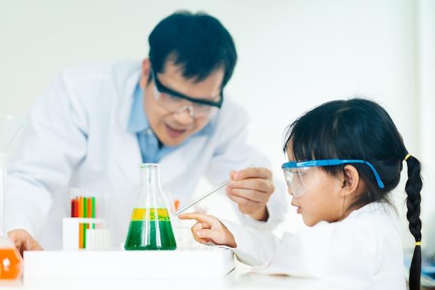 A menina e o professor asiáticos fazem um experimento sobre a separação de fases de óleo e água.