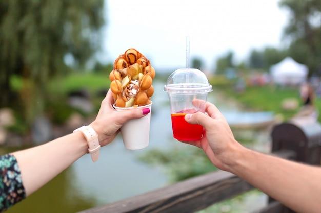 A menina e o sujeito durante a caminhada têm nas mãos um copo de papel com um waffle belga e uma bebida fresca em um parque verde