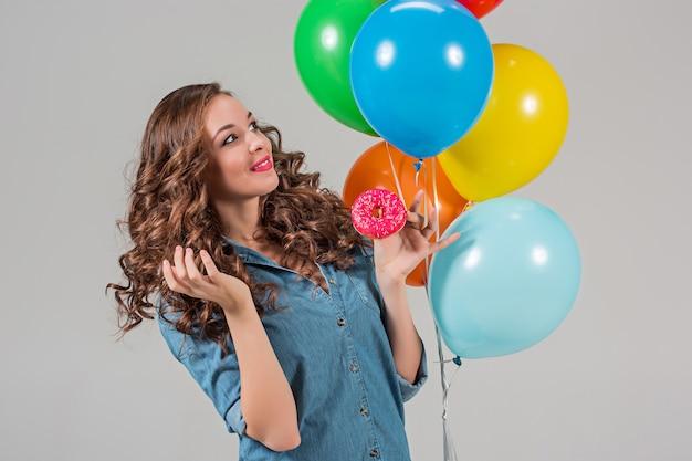 A menina e um monte de balões coloridos na parede cinza