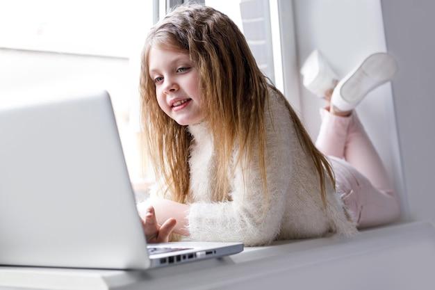 A menina em casa se comunica na internet em casa