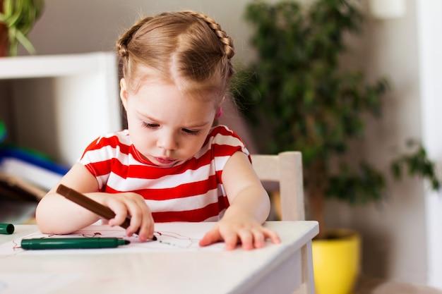 A menina em casa se senta à mesa e desenha com marcadores