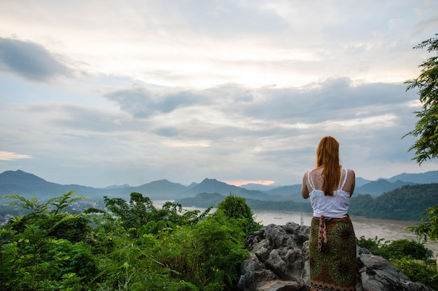 A menina em pé volte para ver a vista de luang prabang.
