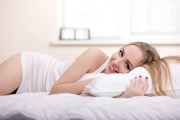 A menina em roupa interior encontra-se em uma cama e sorri.