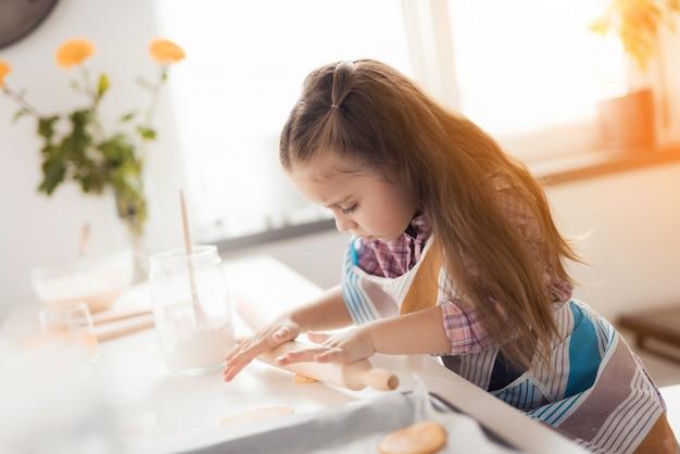 A menina em sua cozinha prepara biscoitos caseiros