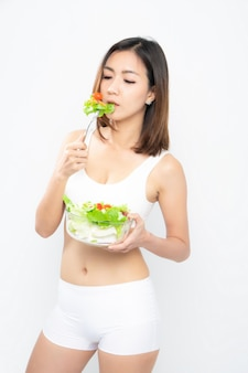 A menina em um sutiã branco do esporte prende uma bacia de salada.